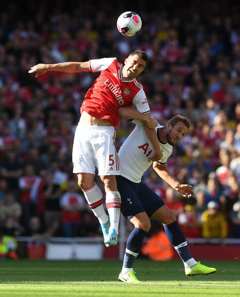 LONDON, ENGLAND - SEPTEMBER 01: Sokratis of Arsenal heads the ball under pressure from Harry Kane of Tottenham during the Premier League match between Arsenal FC and Tottenham Hotspur at Emirates Stadium on September 01, 2019 in London, United Kingdom