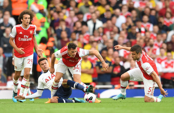 LONDON, ENGLAND - SEPTEMBER 01: Granit Xhaka of Arsenal is challenged by Dele Alli of Tottenham as Sokratis look on during the Premier League match between Arsenal FC and Tottenham Hotspur at Emirates Stadium on September 01, 2019 in London, United Kingdom