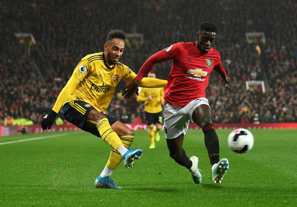 MANCHESTER, ENGLAND - SEPTEMBER 30: Pierre-Emerick Aubameyang of Arsenal crosses the ball under pressure from Axel Tuanzebe of Man Utd during the Premier League match between Manchester United and Arsenal FC at Old Trafford on September 30