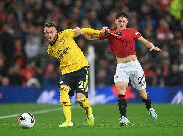 MANCHESTER, ENGLAND - SEPTEMBER 30: Calum Chambers of Arsenal passes the ball under pressure from Daniel James of Man Utd during the Premier League match between Manchester United and Arsenal FC at Old Trafford on September 30, 2019 in Manchester, United Kingdom