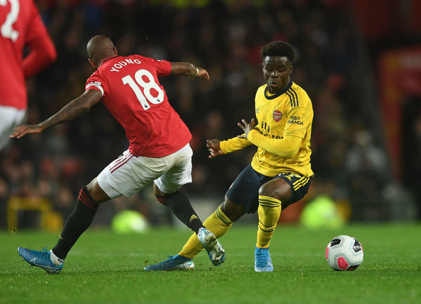 MANCHESTER, ENGLAND - SEPTEMBER 30: Bukayo Saka of Arsenal takes on Ashley Young of Man Utd during the Premier League match between Manchester United and Arsenal FC at Old Trafford on September 30, 2019 in Manchester, United Kingdom