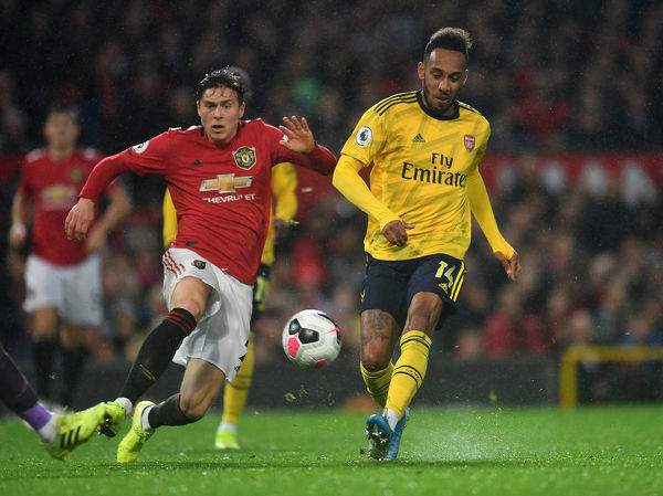 MANCHESTER, ENGLAND - SEPTEMBER 30: Pierre-Emerick Aubameyang scores Arsenal's goal under pressure from Victor Lindelof of Man Utd during the Premier League match between Manchester United and Arsenal FC at Old Trafford on September 30, 2019 in Manchester, United Kingdom