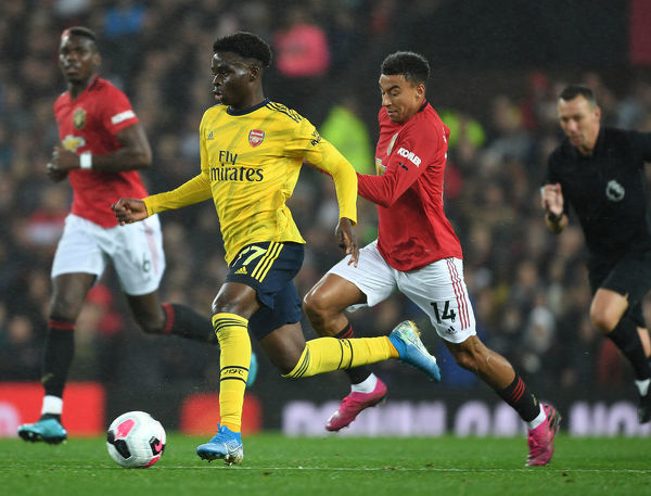 MANCHESTER, ENGLAND - SEPTEMBER 30: Bukayo Saka of Arsenal challenged by Ashley Young of Man United during the Premier League match between Manchester United and Arsenal FC at Old Trafford on September 30, 2019 in Manchester, United Kingdom