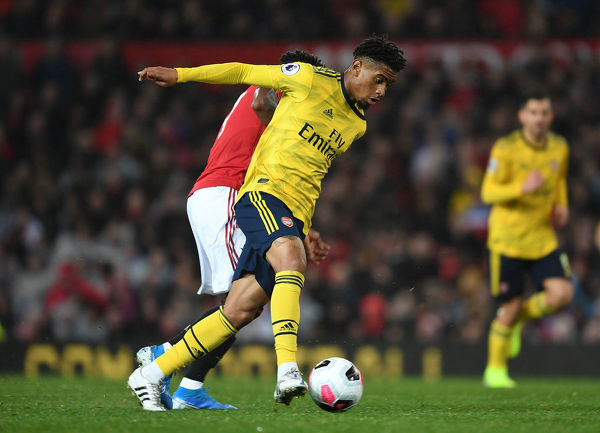 MANCHESTER, ENGLAND - SEPTEMBER 30: Reiss Nelson of Arsenal breaks past Fred of Man United during the Premier League match between Manchester United and Arsenal FC at Old Trafford on September 30, 2019 in Manchester, United Kingdom