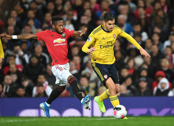 MANCHESTER, ENGLAND - SEPTEMBER 30: Dani Ceballos of Arsenal breaks past Fred of Man United during the Premier League match between Manchester United and Arsenal FC at Old Trafford on September 30, 2019 in Manchester, United Kingdom