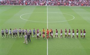 The Arsenal and Newcastle team shake hands before the match