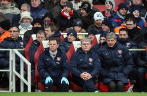 Arsene Wenger the Arsenal Manager sits on the bench with Pat Rice (Assistant Manager)
