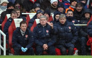 Arsene Wenger the Arsenal Manager sits in the dug out with Pat Rice (Assistant Manager)