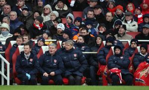 Arsene Wenger the Arsenal Manager sits in the dug out with Pat Rice (Assistant)