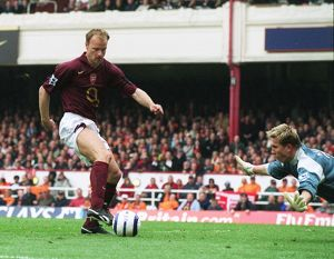 dennis bergkamp takes the ball away from neil clement