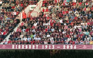 Fans in the North Bank sit above the 1913 - 2006 banner