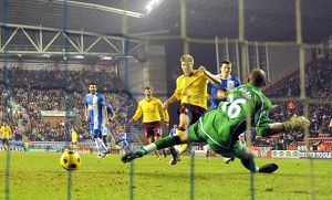 nicklas bendtner shoots past wigan goalkeeper ali al