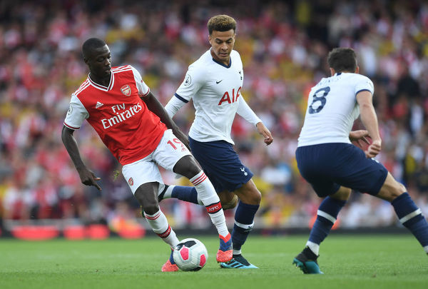 LONDON, ENGLAND - SEPTEMBER 01: Nicolas Pepe of Arsenal takes on Dele Alli and Harry Winks of Tottenham during the Premier League match between Arsenal FC and Tottenham Hotspur at Emirates Stadium on September 01, 2019 in London, United Kingdom