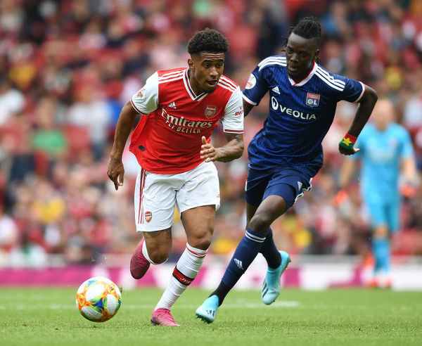 LONDON, ENGLAND - JULY 28: Reiss Nelson of Arsenal breaks past Bertrand Traore of Lyon during the Emirates Cup match between Arsenal and Olympic Lyonnais at Emirates Stadium on July 28, 2019 in London, England