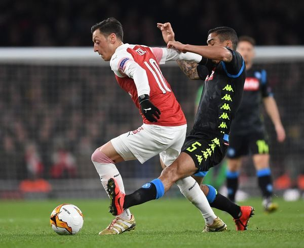 LONDON, ENGLAND - APRIL 11: Mesut Ozil of Arsenal holds off Allan of Napoli during the UEFA Europa League Quarter Final First Leg match between Arsenal and S