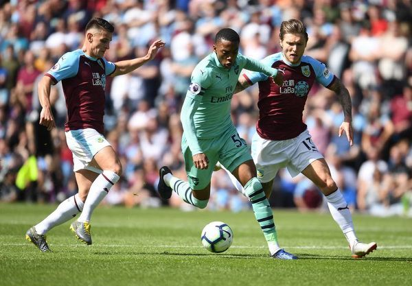 BURNLEY, ENGLAND - MAY 12: Joe Willock of Arsenal breaks past (L) Ashley Westwood and (R) Jeff Hendrick of Burnley during the Premier League match between Burnley FC and Arsenal FC at Turf Moor on May 12, 2019 in Burnley, United Kingdom
