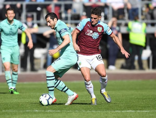 BURNLEY, ENGLAND - MAY 12: Henrikh Mkhitaryan of Arsenal breaks past Ashley Westwood of Burnley during the Premier League match between Burnley FC and Arsenal FC at Turf Moor on May 12, 2019 in Burnley, United Kingdom