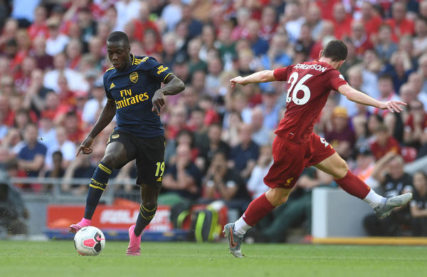 LIVERPOOL, ENGLAND - AUGUST 24: Nicolas Pepe of Arsenal skips past Andy Robertson of Liverpool during the Premier League match between Liverpool FC and Arsenal FC at Anfield on August 24, 2019 in Liverpool, United Kingdom
