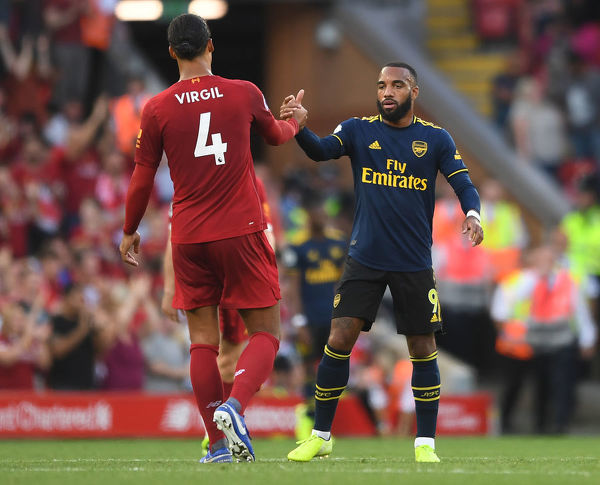 LIVERPOOL, ENGLAND - AUGUST 24: Alexandre Lacazette of Arsenal high fives Virgil van Dijk of Liverpool after the Premier League match between Liverpool FC and Arsenal FC at Anfield on August 24, 2019 in Liverpool, United Kingdom