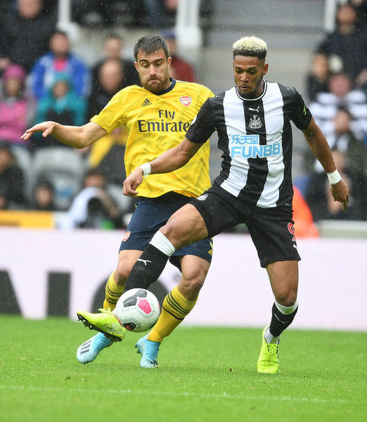 NEWCASTLE UPON TYNE, ENGLAND - AUGUST 11: Sokratis of Arsenal challenges Joelinton of Newcastle during the Premier League match between Newcastle United and Arsenal FC at St. James Park on August 11, 2019 in Newcastle upon Tyne, United Kingdom