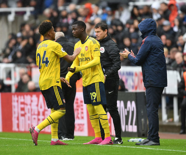 NEWCASTLE UPON TYNE, ENGLAND - AUGUST 11: (R) Arsenal substitute Nicolas Pepe comes on for (L) Reiss Nelson during the Premier League match between Newcastle United and Arsenal FC at St. James Park on August 11, 2019 in Newcastle upon Tyne, United Kingdom
