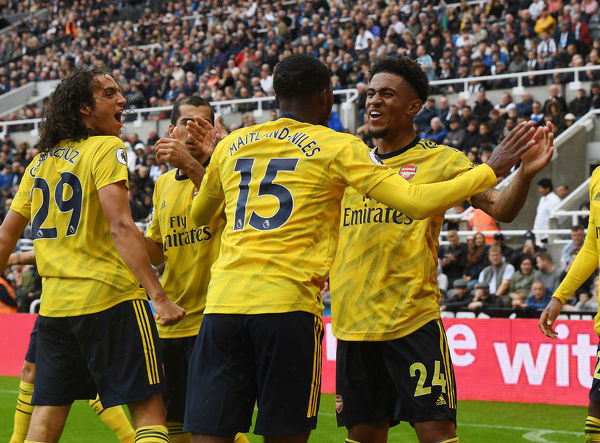 NEWCASTLE UPON TYNE, ENGLAND - AUGUST 11: (L-R) Matteo Guedouzi, Ainsley Maitland-Niles and Reiss Nelson celebrate the Arsenal goal during the Premier League match between Newcastle United and Arsenal FC at St. James Park on August 11