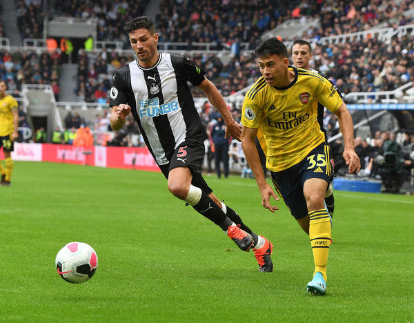 NEWCASTLE UPON TYNE, ENGLAND - AUGUST 11: Gabriel Martinelli of Arsenal takes on Fabian Schar of Newcastle during the Premier League match between Newcastle United and Arsenal FC at St. James Park on August 11, 2019 in Newcastle upon Tyne, United Kingdom