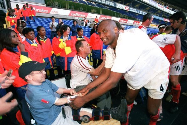 Patrick Vieira celebrates at the end of the match with a disabled fan