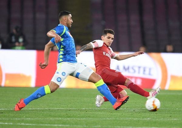 NAPLES, ITALY - APRIL 18: Lucas Torreira of Arsenal takes on Faouzi Ghoulam of Napoli during the UEFA Europa League Quarter Final Second Leg match between S.S.C. Napoli and Arsenal at Stadio San Paolo on April 18, 2019 in Naples, Italy