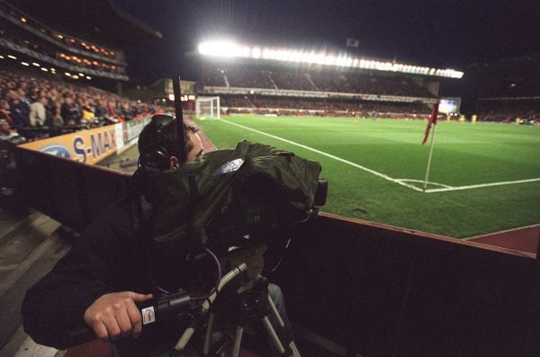 a tv cameraman works under the floodlights