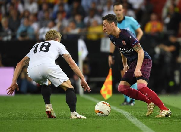 VALENCIA, SPAIN - MAY 09: Mesut Ozil of Arsenal takes on Daniel QWass of Valencia during the UEFA Europa League Semi Final Second Leg match between Valencia and Arsenal at Estadio Mestalla on May 09, 2019 in Valencia, Spain