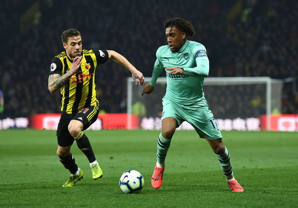 WATFORD, ENGLAND - APRIL 15: Alex Iwobi of Arsenal takes on Kiko Femenia of Watford during the Premier League match between Watford FC and Arsenal FC at Vicarage Road on April 15, 2019 in Watford, United Kingdom