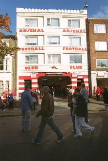 Arsenal fans walk outside the entrance to the West Stand Upper before the match