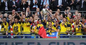 the arsenal players lift the fa cup after the match