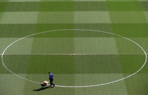 Groundsman Paul Burgess marks out the pitch before the match