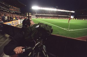 A TV Cameraman works under the floodlights which are on for the last time